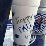collegiate styrofoam cups with footballs scattered